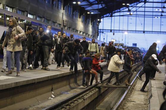 철도 파업이 시작된 프랑스 리옹역에서 승객들이 출근 시간대 레일을 건너가고 있다. [AP=연합뉴스]