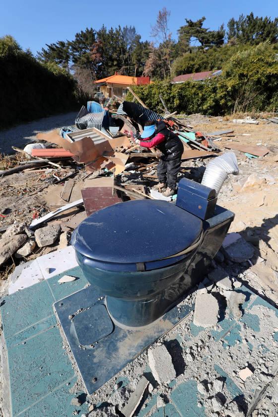 지난해 12월 13일 오후 지진으로 피해를 본 경북 포항시 북구 흥해읍 한 주택에서 인근 주민이 철거 잔해를 정리하고 있다. [연합뉴스]