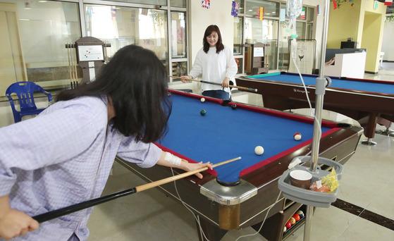 3일 부산진구 온종합병원 병원학교에서 이유진 봉사단장(왼쪽 사진 오른쪽)이 환우와 포켓볼을 치고 있다. [송봉근 기자]