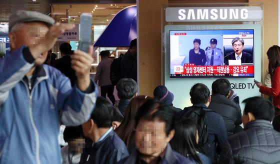 6일 오후 서울역에서 시민들이 박근혜 전 대통령 '국정농단' 사건의 1심 선고공판 생중계를 시청하고 있다. [연합뉴스]