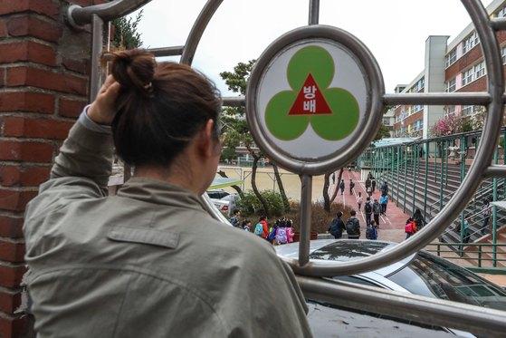 3일 오전 서울 서초구 방배초등학교에서 한 학부모가 자녀의 등교 모습을 바라보고 있다. 이곳에서는 하루 전인 2일 20대 남성이 학교로 들어가 4학년 여아(10)의 목에 흉기를 댄 채 인질극이 벌어졌다가 출동한 경찰에 의해 1시간 만에 검거된 사건이 있었다. [뉴스1]