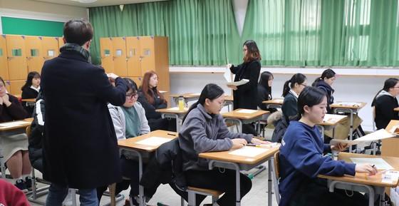 2018학년도 대학수학능력시험일인 23일 오전 제주 중앙여자고등학교에 마련된 고사장에서 감독관이 1교시 국어영역 문제지를 나눠주고 있는 모습. [뉴스1]