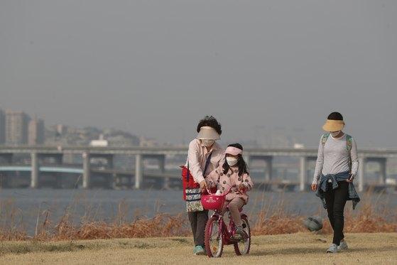 중국발 황사 등 영향으로 수도권 지역의 미세먼지 농도가 '나쁨'을 기록한 지난달 29일 오후 서울 서초구 반포한강시민공원에서 가족 나들이객이 마스크를 쓰고 산책을 하고 있다. [뉴스1]