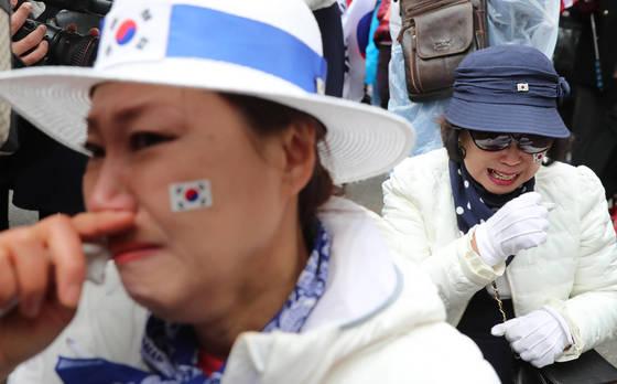 박근혜 전 대통령 1심 선고일인 6일 오후 서초구 서울중앙지법 앞에서 박 전 대통령의 지지자들이 1심 선고 결과를 확인한 뒤 눈물을 흘리고 있다. [사진 연합뉴스]