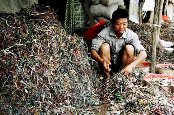 중국은 더 이상 세계의 쓰레기통이 되지 않겠다며 폐기물 수입 중단을 추진하고 있다. 사진은 2005년 광동 구이유 지역의 폐전선 처리 업체. [EPA=연합뉴스]