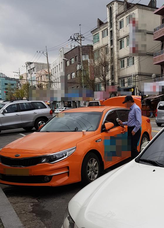지난 6일 서울 강북구의 한 기사식당 앞에서 서울시의 유니폼 셔츠를 입은 운전사가 모자를 깊게 눌러 쓰고 있다. 임선영 기자