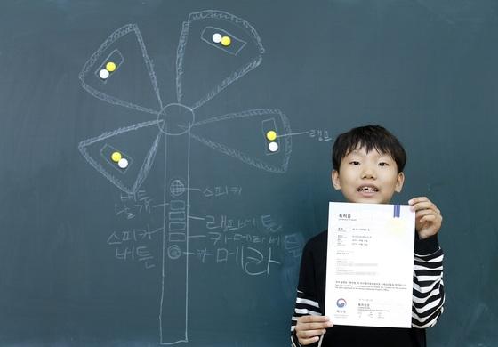 '휴대용 방범 기구'를 발명해 특허까지 받은 대구북부초등학교 4학년 신준협(10)군이 특허증을 들어 보이고 있다. 칠판에는 바람개비에 조명을 붙이고, 여러가지 기능을 탑재한 버튼 등 '휴대용 방범 기구'를 설명하는 밑그림이 보인다. [사진 프리랜서 공정식]