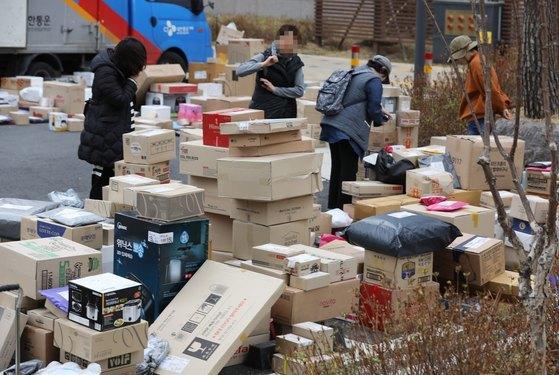 10일 오후 경기도 남양주 다산신도시의 한 아파트단지 주차장에서 주민들이 택배를 찾아가고 있다. [뉴스1]