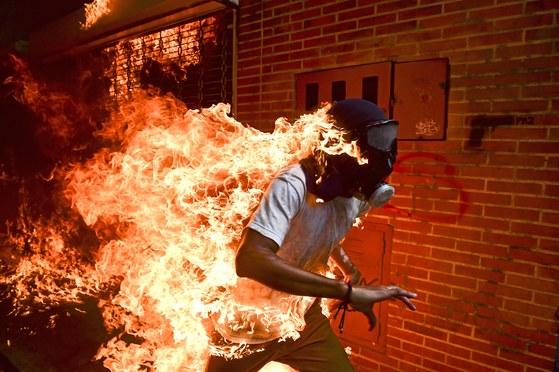 올해의 사진을 수상한 '베네수엘라의 위기' . 작년 5월 마두로 대통령에 반대하는 반 정부 시위대가 화염에 휩싸여 도망치는 장면을 AFP통신 사진기자 로날도 슈미트가 포착했다. 스팟 뉴스 부문 1위에도 선정됐다. [연합뉴스]