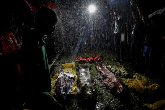 정부의 탄압을 피해 방글라데시로 피난하던 중 보트가 침몰해 사망한 로힝야족 난민의 시신이 폭우가 쏟아지는 가운데 놓여 있다. 지난해 9월 28일 촬영됐다. [로이터=연합뉴스]