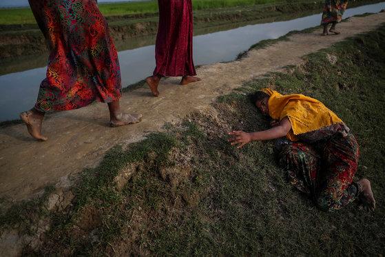 지난해 11월 2일 방글라데시로 피난하던 로힝야족 난민이 기운을 잃고 쓰려져 도움을 요청하고 있다.[로이터=연합뉴스]