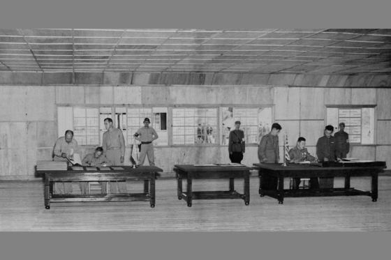 1953년 7월 27일 판문점에서 정전협정 문서에 서명하고 있는 윌리엄 해리슨 2세(왼쪽) 유엔측 대표와 남일(오른쪽) 공산측 대표.  [중앙포토]