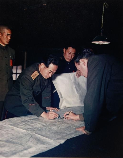1951년 11월 27일 판문점에서 열린 휴전회담에 참석한 공산군연락장교 장춘산(Chang Chun San) 대령(왼쪽)과 유엔연락장교 제임스 머레이(James C. Murray) 대령(오른쪽)이 양측의 합의하에 군사분계선을 지도상에 가조인 하고 있다. [사진 국사편찬위원회 캡쳐]