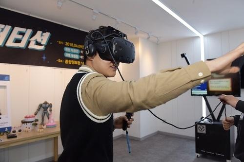 VR컴퍼티션에서 '케이크 줍기' VR게임을 즐기는 학생