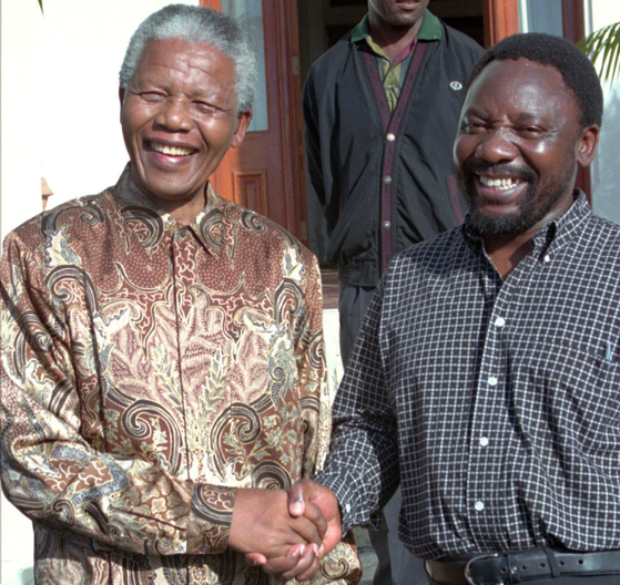 FILE - In this April 13, 1996 file photo South African President Nelson Mandela, left, shakes hands with the ANC Secretary General, Cyrill Ramaphosa, after Mandela announced Ramaphosa's resignation as a Member of Parliament, in Cape Town, South Africa. Ramaphosa now faces the challenge of leading one of Africa's most powerful economies out of a swamp of corruption scandals that bought down former leader Jacob Zuma. (AP Photo, File) <저작권자(c) 연합뉴스, 무단 전재-재배포 금지>