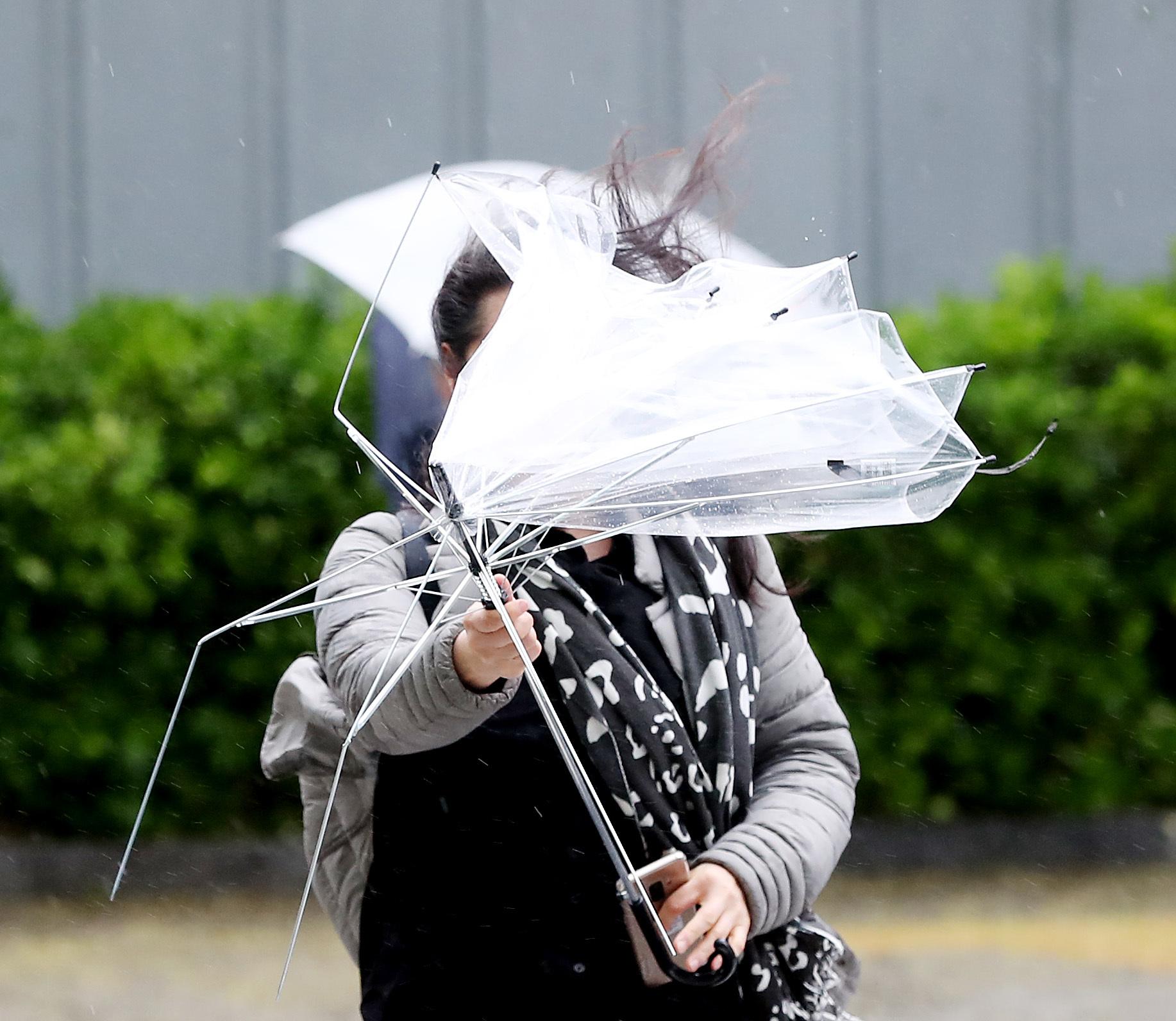 전국 대부분 지역에 비가 내린 23일 오전 서울 외교부 인근에서 한 시민이 갑자기 불어온 돌풍에 비닐이 거의 다 벗겨진 우산을 잡고 건널목을 건너고 있다. 우상조 기자