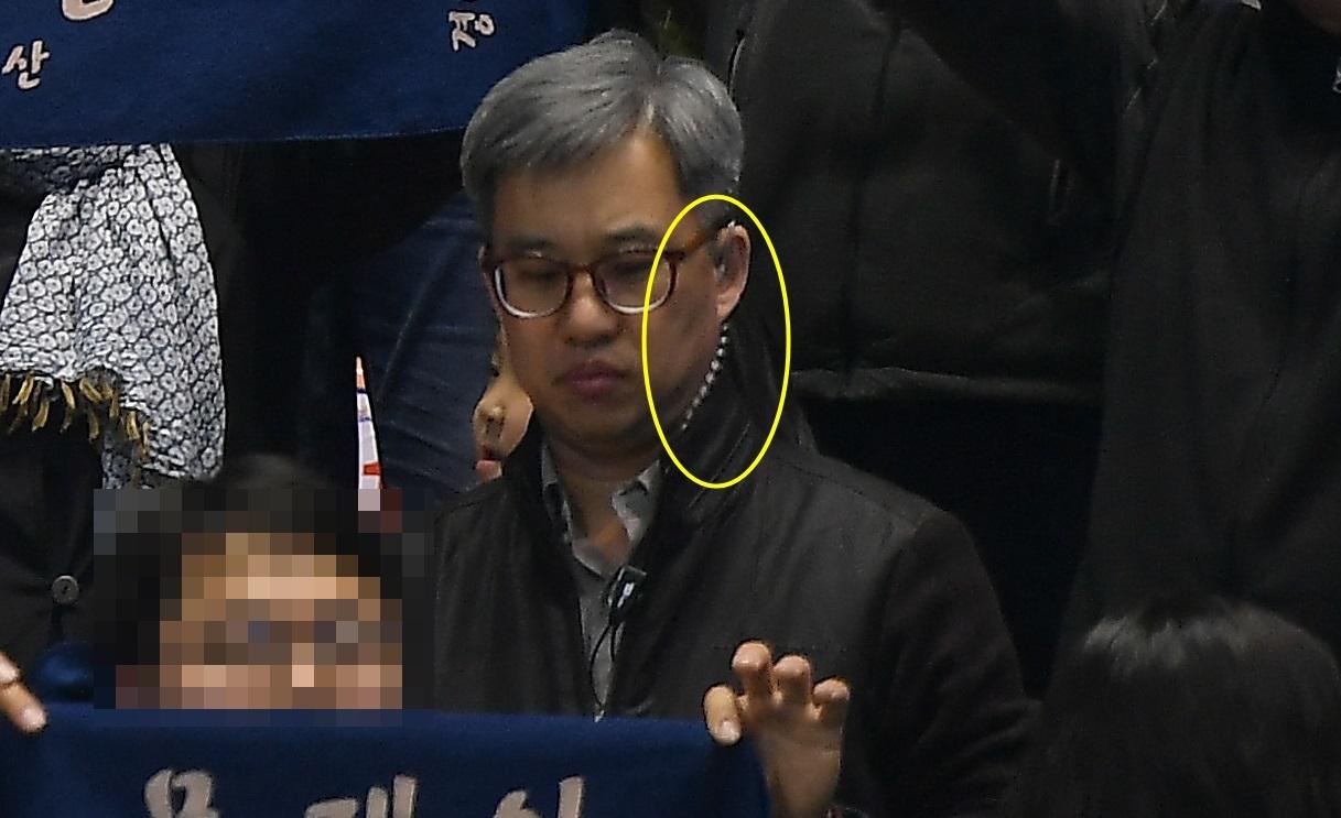 더불어민주당원 댓글조작 사건의 핵심 피의자인 '드루킹' 김동원(49)씨가 작년 3월 31일 부산 연제구 부산실내체육관에서 열린 더불어민주당 영남권 대선 경선 현장에서 왼쪽 귀에 '이어마이크'를 꽂은 모습이 보인다. [사진 뉴데일리]