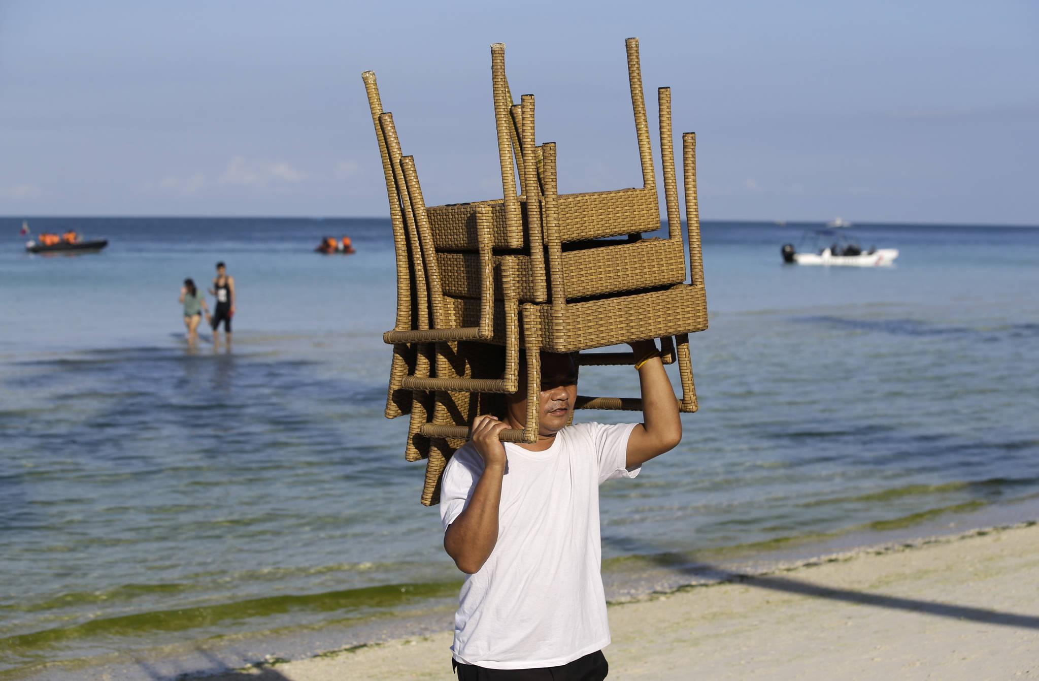 25일 폐쇄를 하루 앞둔 필리핀 보라카이섬. 한 관광업계 종사자가 의자를 치우고 있다. [사진 AP]