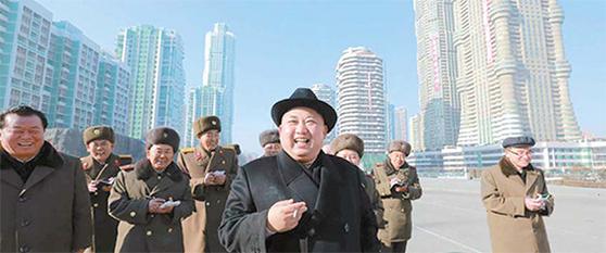 김정은 북한 국무위원장이 지난해 1월 평양 뉴타운인 여명거리 건설 현장을 돌아보고 있다. 2016년 4월 착공돼 1년 만에 완공한 이곳엔 70층짜리주상복합 아파트를 비롯해 44개 동, 4804가구의 고층 아파트가 들어섰다. [연합뉴스]