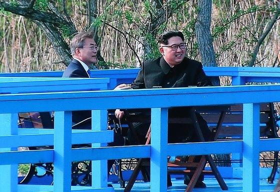 27일 오후 경기도 고양시 킨텍스에 마련된 2018남북정상회담 프레스센터에 문재인 대통령과 김정은 북한 국무위원장이 기념식수 후 도보다리에서 독대하는 모습이 생방송 중계되고 있다.