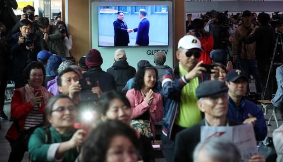 27일 오전 서울역에서 문재인 대통령과 김정은 북한 국무위원장의 만남을 지켜보는 시민들이 박수를 치거나 휴대전화로 촬영하고 있다. [사진 뉴시스]