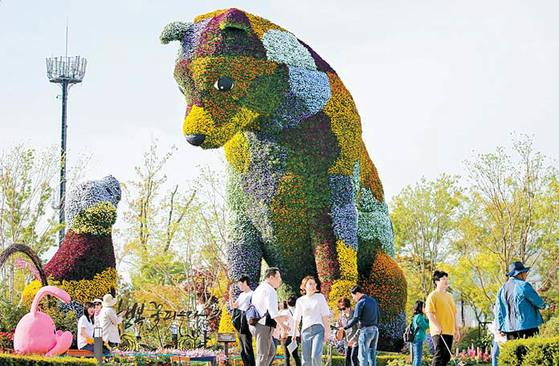 5월 22일까지 열리는 '봄꽃축제'를 보기 위해 순천만정원을 찾은 상춘객들이 개 모양을 형상화한 꽃 조형물 앞에서 사진을 찍고 있다. 프리랜서 장정필