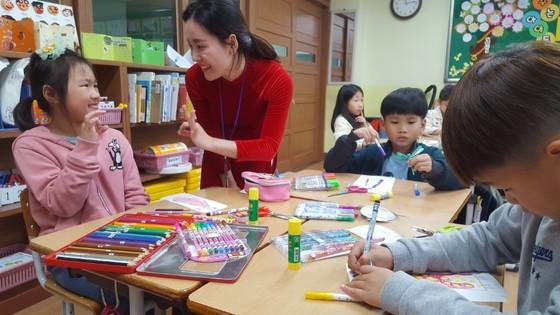 베트남인 응우이엔 티 탄투 교사가 베트남 전통복인 아오자이 칠하기를 끝낸 울산 언양초교 학생과 간단한 영어, 손짓으로 대화하고 있다. 최은경 기자
