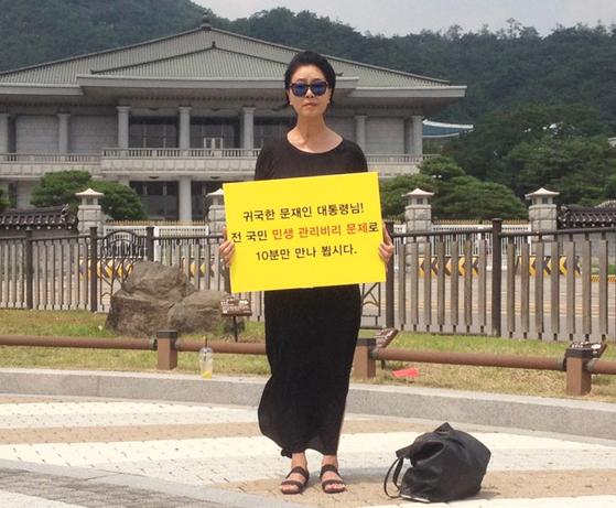 지난해 7월 배우 김부선 씨가 문재인 대통령에게 아파트 관리비 비리 문제 해결을 요구하면서 1인시위를 벌이고 있다.[연합]