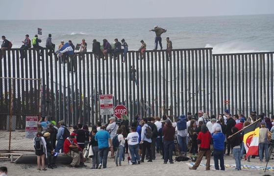 이민자 캐러밴 행렬에 참가한 사람들이 29일(현지시간) 미국-멕시코 국경에 올라가 시위를 벌이는 가운데 이를 지지하는 미국 쪽 시위대가 이들을 맞이하고 있다. [AFP=연합뉴스]