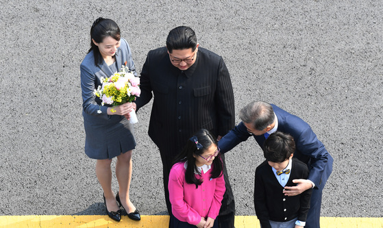 문재인 대통령과 북한 김정은 국무위원장이 27일 오전 판문점에서 화동에게 꽃을 받은 뒤 격려하고 있다. 왼쪽 김여정 당 중앙위 제1부부장이 김정은 위원장이 전한 꽃을 받아들고 있다. 김상선 기자