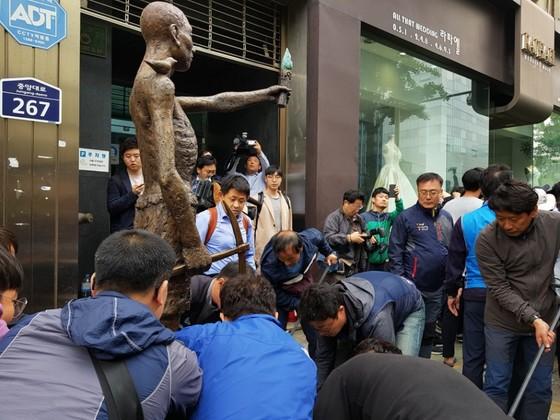 시민단체 회원 20여명이 1일 오전 9시 40분 지렛대를 이용해 일본총영사관 앞으로 노동자상을 이동하고 있다. 이은지 기자