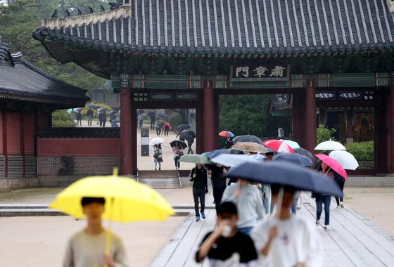 봄비가 내린 2일 오후 서울 종로구 창덕궁을 찾은 시민들이 우산을 쓰고 경내를 걷고 있다. [뉴시스]