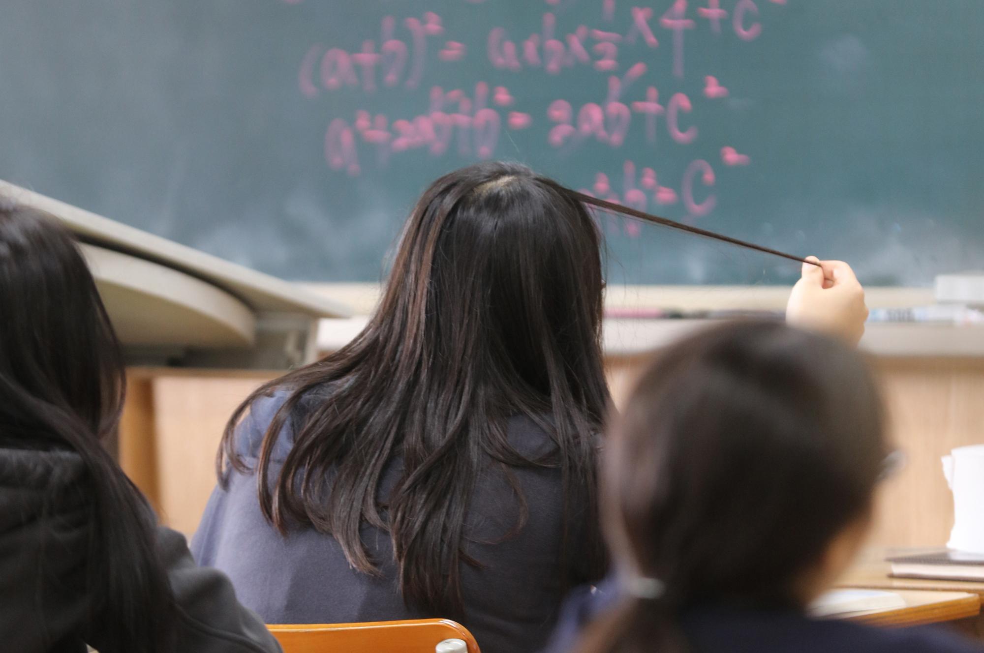 서울의 한 중학교에서 여학생이 수업 도중 머리를 만지고 있다. [연합뉴스]