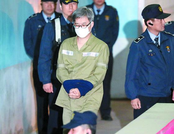 """'민주당원 댓글 조작 사건'으로 구속된 파워블로거 '드루킹' 김동원씨의 첫 재판이 2일 오전 서울 서초동 서울중앙지법에서 열렸다. 김씨는 재판장이 공소 사실을 인정하는지 묻자 '네 인정합니다""""라고 답했다. 연녹색 수의를 입은 김씨가 호송차에서 내려 법정으로 이동하고 있다. [최승식 기자]"""