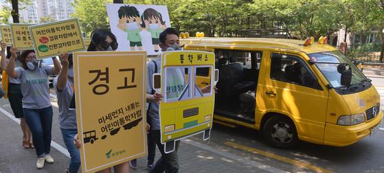 환경정의 관계자들이 미세먼지 저감을 위한 어린이 통학차량 관리 캠페인을 하고 있다. [뉴시스]