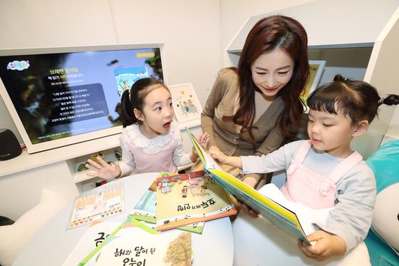 3일 서울 광화문 KT스퀘어에서 홍보모델이 어린이들과 함께 KT와 대교가 손잡고 출시한 국내 최초 AI 동화 서비스 '소리동화'를 시연하고 있다. [사진 KT]