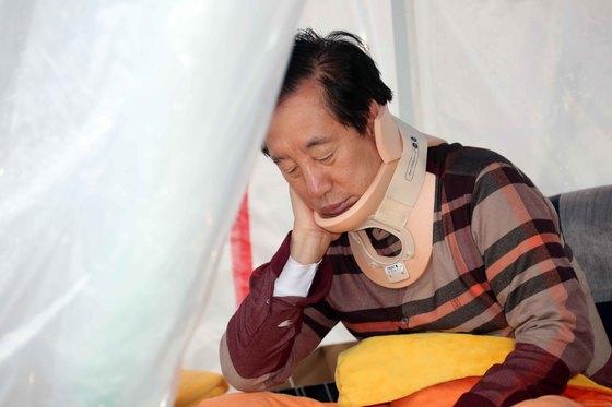 5일 30대 남성으로부터 폭행을 당한 자유한국당 김성태 원내대표가 6일 국회 농성장으로 돌아와 단식투쟁을 이어가고 있다. 김 원내대표가 통증 부위를 만지고 있다. 변선구 기자