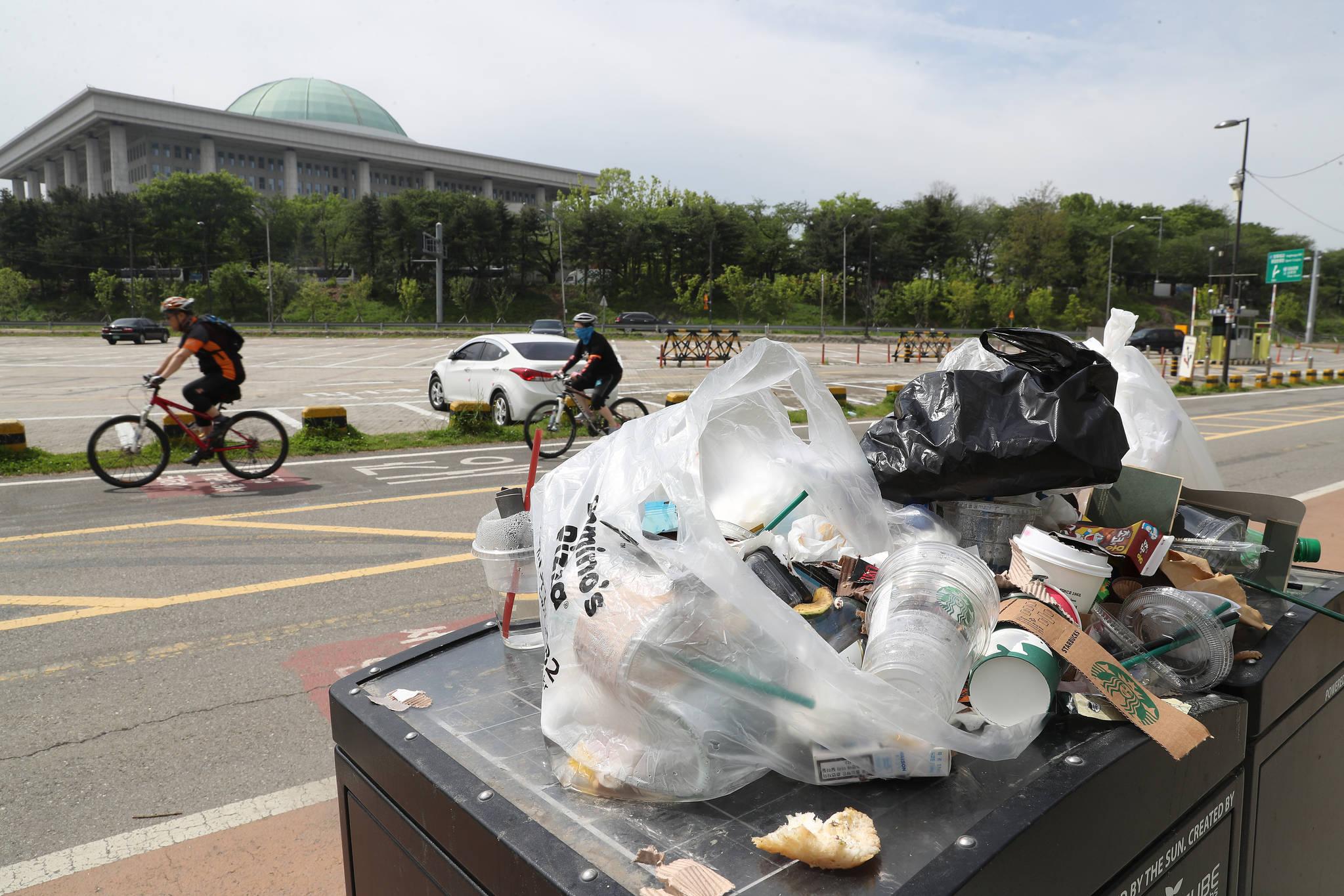 3일동안 이어진 연휴 마지막날인 7일 서울 여의도 한강 시민공원에서 자전거를 타며 휴일을 즐기는 시민들 앞쪽에 마구 버려진 쓰레기들이 놓여있다. 우상조 기자