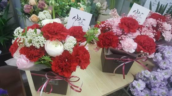 어버이날 마을 회관은 자식들이 보내온 꽃다발과 축전을 갖고 나와 자랑하며 행복해하기 바쁘다. [중앙포토]