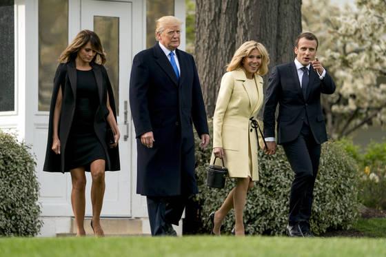 지난달 23일(현지시간) 미국을 국빈 방문한 에마뉘엘 마크롱 부부(오른쪽)가 백악관 건물 앞에서 다정하게 손을 잡고 있다. 살짝 거리를 두고 걷는 도널드 트럼프 부부와는 대조적인 모습이다. [AP=연합뉴스]