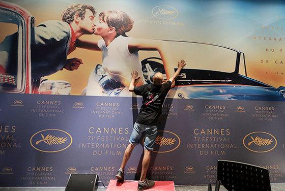 제71회 칸영화제 개막을 앞두고 기자회견장에 작업자가 공식 포스터를 설치하고 있다. 포스터 속 배우는 영화 '미치광이 삐에로'의 장 폴 벨몽도, 안나 카리나. [로이터=연합뉴스]