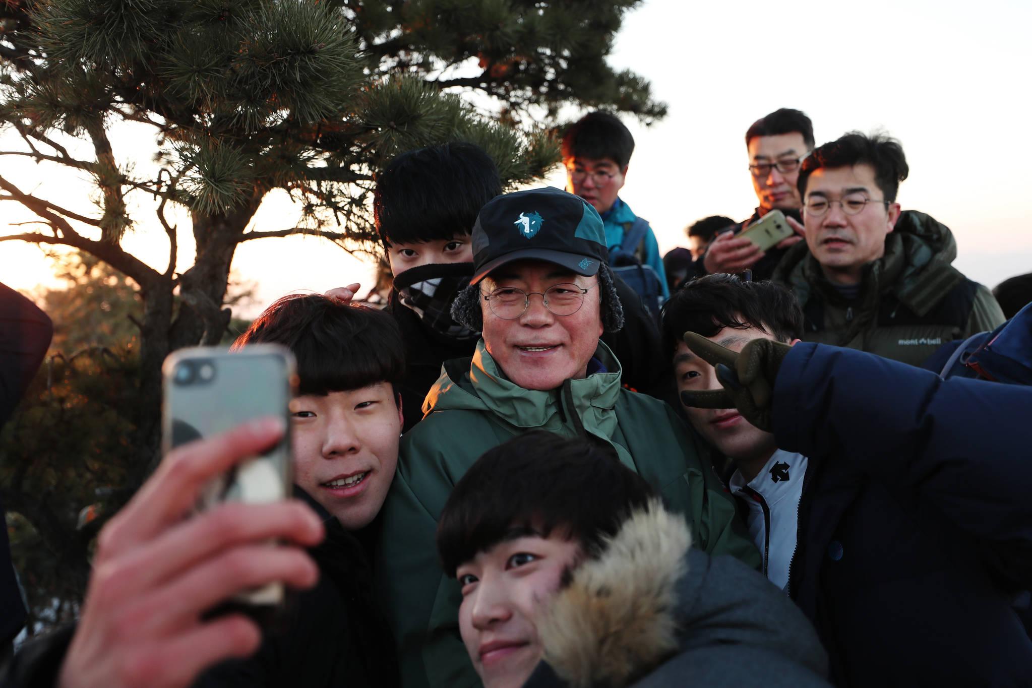 1월 1일 2017년을 빛낸 의인 6명과 북한산 산행에 나선 문재인대통령이 사모바위에서 새해 첫 일출을 배경으로 기념촬영을 하고 있다. [사진 청와대]