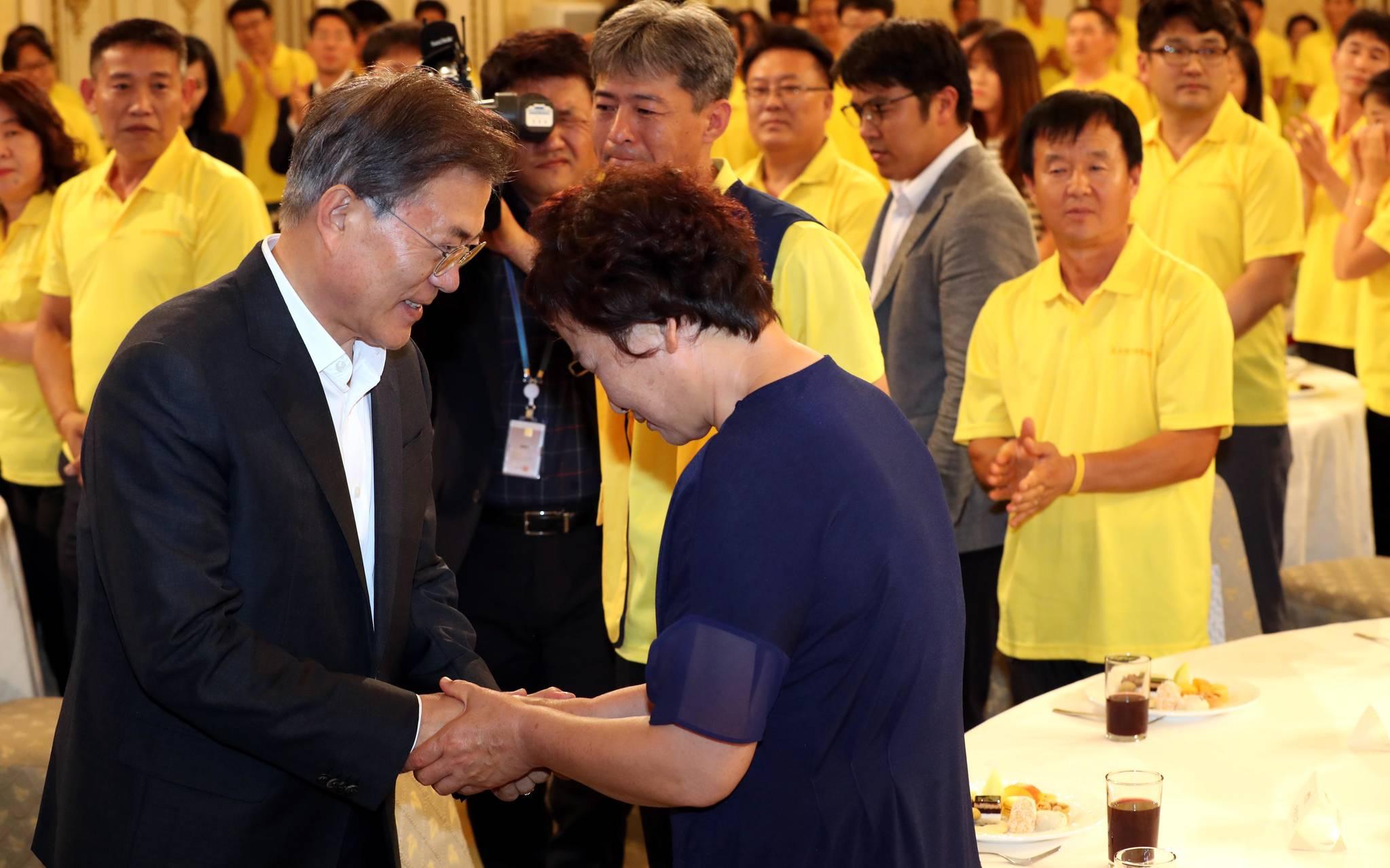 문재인 대통령이 지난해 8월16일 오후 청와대 영빈관에서 열린 4.16 세월호 참사 피해자 가족 초청 간담회에서 한 참석자의 손을 잡아주고 있다. 김상선 기자