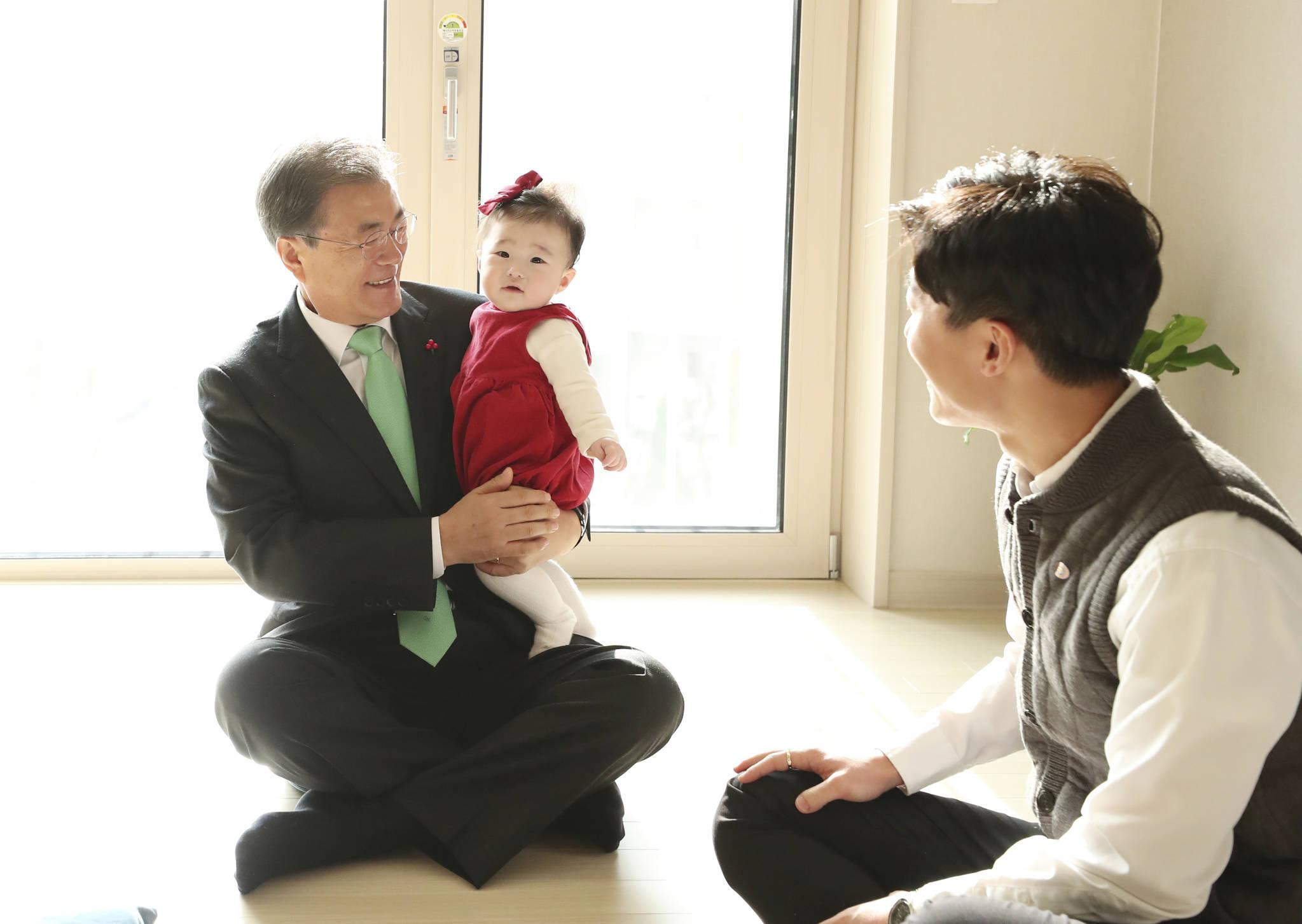 문재인 대통령이 지난해 12월 7일 서울 노원구 '노원 에너지제로 주택 오픈하우스'행사에 참석했다. 문 대통령이 한 신혼부부 입주세대를 방문해 아이를 안아 주고 있다. 김상선 기자