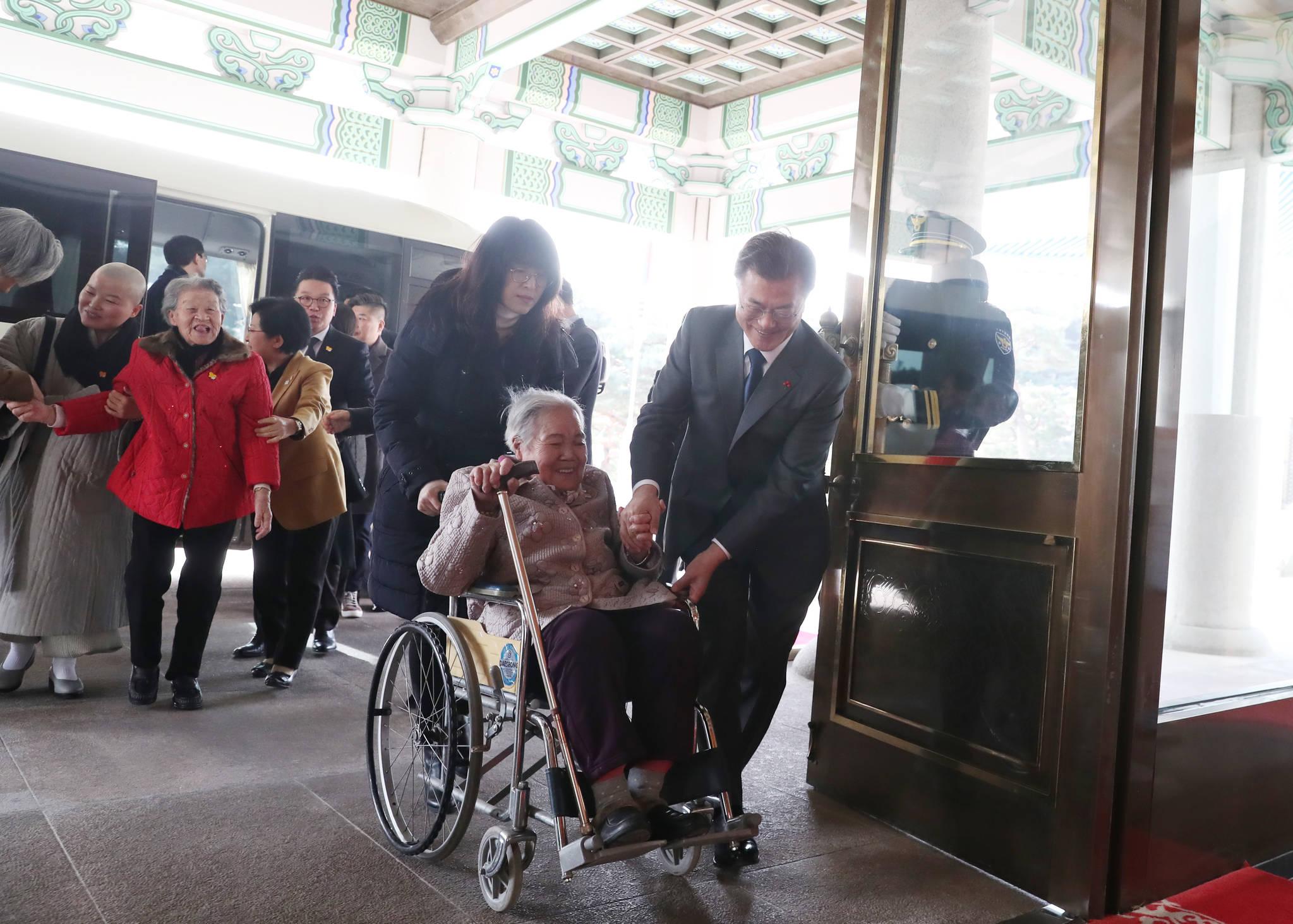 문재인 대통령은 1월 4일 일본군 위안부 피해자들을 청와대로 초청해 오찬을 함께 했다.문 대통령이 늦게 도착한 한 할머니의 휠체어를 밀며 행사장으로 이동하고 있다. [사진 청와대]