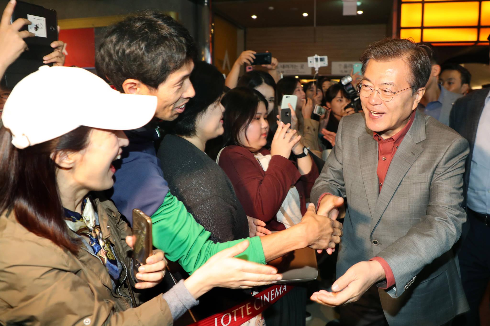 문재인 대통령이 지난해 10월15일 부산국제영화제를 방문해 영화 '미씽'을 관람한 뒤 관객들과 손을 잡고 있다. 청와대사진기자단