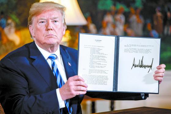 도널드 트럼프 미국 대통령이 8일 백악관에서 미국의 이란 핵 협정 탈퇴를 공식 선언하고 독자 제재를 명령한 문서를 펼쳐 보이고 있다. [신화=연합뉴스]