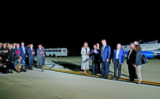 도널드 트럼프 미국 대통령이 10일 워싱턴DC 앤드루스 공군기지에서 북한에서 석방된 한국계 미국인 3명과 기자회견을 하고 있다. 이날 백악관 존 볼턴 국가안보보좌관(왼쪽 셋째)과 세라 샌더스 대변인(왼쪽 첫째)도 이 자리에 참석했다. [로이터=연합뉴스]