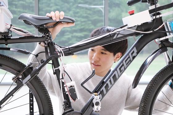 완성 단계인 대한민국 1호 자율주행 자전거. 송씨가 자전거를 살펴보고 있다. [사진 포스텍]