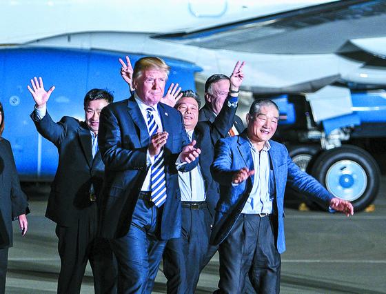 """북한에 억류돼 있다 석방된 한국계 미국인 3명이 10일(현지시간) 미국 워싱턴DC 앤드루스 공군기지를 통해 귀환했다. 도널드 트럼프 대통령이 이날 귀환한 김상덕(왼쪽), 김학송, 김동철씨(왼쪽 셋째·다섯째)와 함께 활주로를 걸어 나오고 있다. 왼쪽 넷째는 이들의 석방 협상을 이끈 마이크 폼페이오 국무장관. 이날 기자회견에서 김동철씨는 '꿈만 같다. 정말 정말 행복하다""""고 소감을 전했다. [AP=연합뉴스]"""